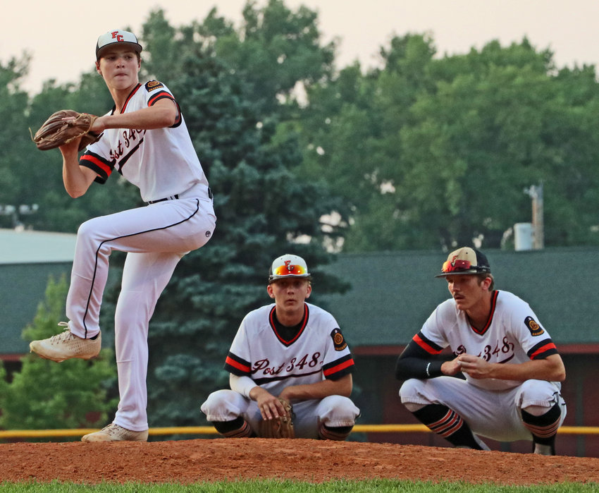 Fort Calhoun Senior Legion pitcher Tanner Jacobson, left, warms up as Ty Hallberg, middle, and Tylan Conner settle in Monday in West Point.