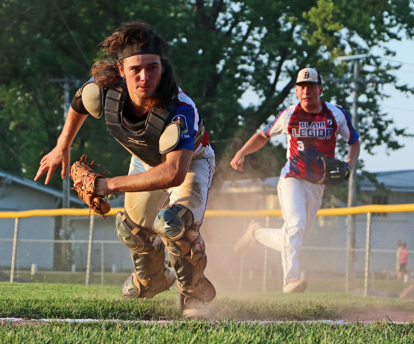 Blair Senior Legion catcher Conner O'Neil, left, tracks down an errant throw home behind the plate as pitcher Tyler Andersen races to cover his position Friday during the Class B Area 3 Tournament in West Point.