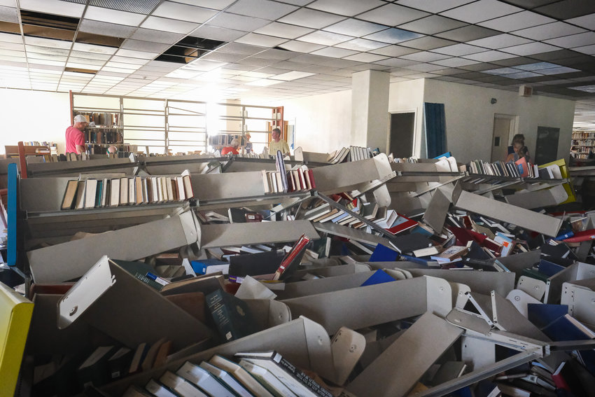 Youth group members from Passageway Church in Blair and the Madrid Evangelical Free Church in Iowa work to reset shelves Wednesday in the Dana-LIFE Library on the Angels Share campus in Blair. The shelves were toppled by vandals a few years ago.