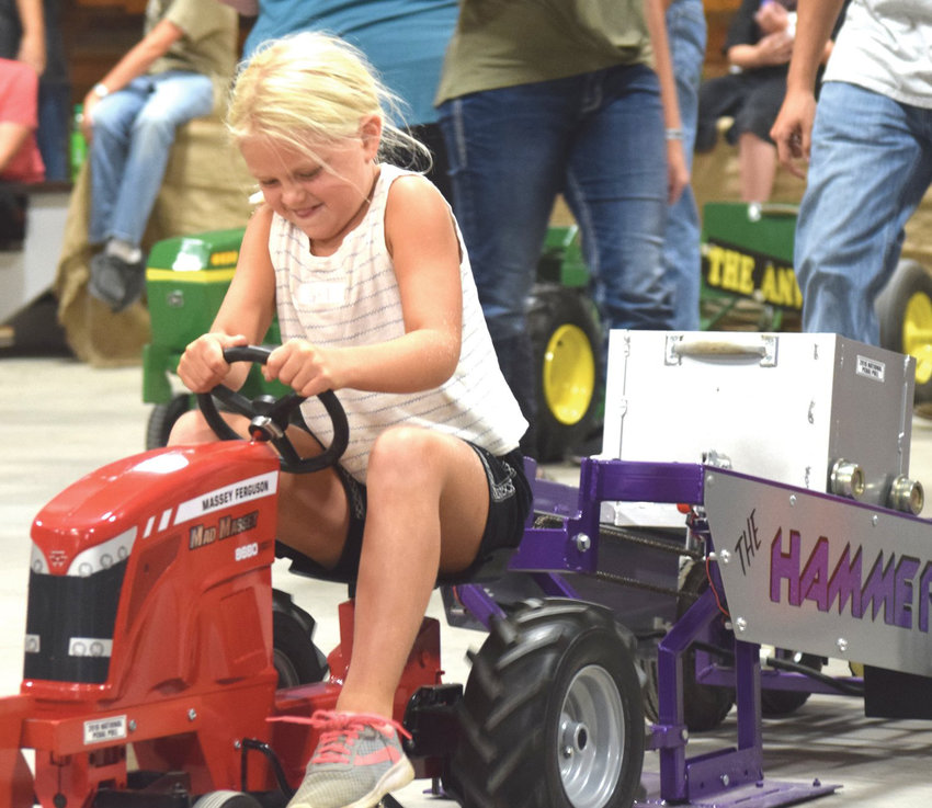 Maddie Nissen concentrates hard at the kiddie tractor pull competition at the Washington County Fair.