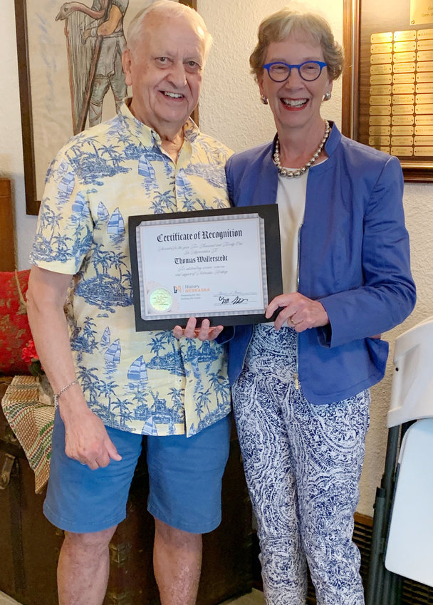 Tom Wallerstedt receives the Heritage Heroes Award given by History Nebraska. One of the Trustees, Pamela Snow of History Nebraska presented Wallerstedt with a certificate and a pin from the organization.