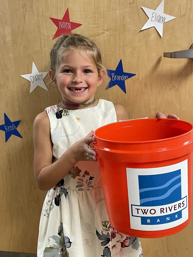 Fort Calhoun Elementary first-grader Stella Christensen poses with a coin bucket Wednesday during school on the first day of the Pioneers For Education's coin drive. The drive will run through Sept. 10.