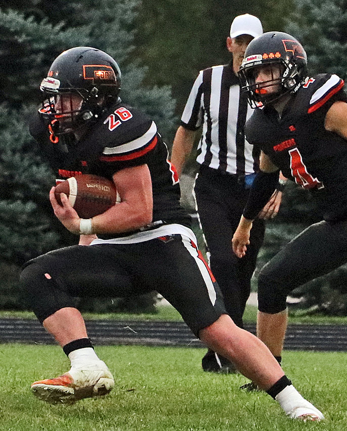 The Pioneers' Clint Dierks, left, makes a cut in front of Ty Hallberg and a referee Sept. 3 at Fort Calhoun High School.