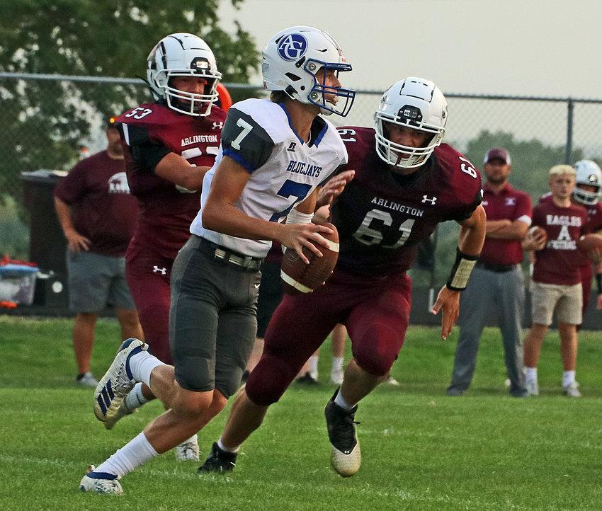 The Eagles' Braden Monke, left, and Josiah Meyer, right, chase after Ashland-Greenwood quarterback Dane Jacobsen on Friday at Arlington High School.