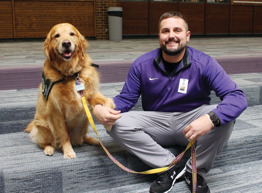 Blair High School special education teacher TJ Bottorf poses for a photo with his therapy dog Teddy. Teddy is the second therapy dog to serve at BHS. The school also has Ted, a golden doodle.