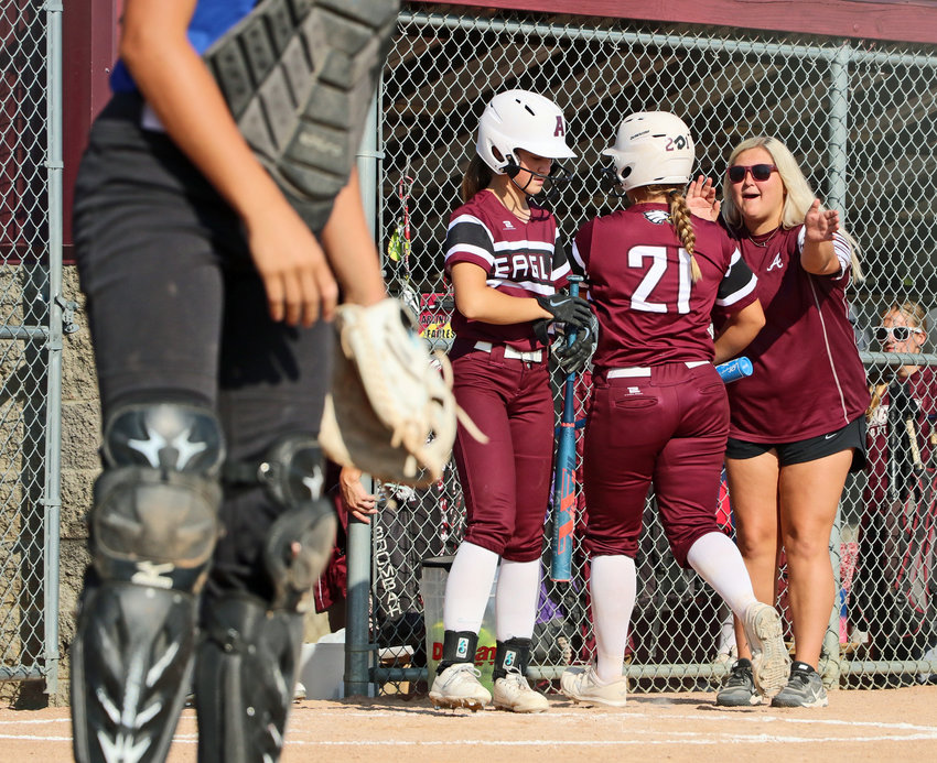 Arlington's Sydney Magnino, left, and assistant coach Alexa Brenn, right, welcome Cadie Robinson back to the dugout after she scored a run Saturday at the Two Rivers Sports Complex.