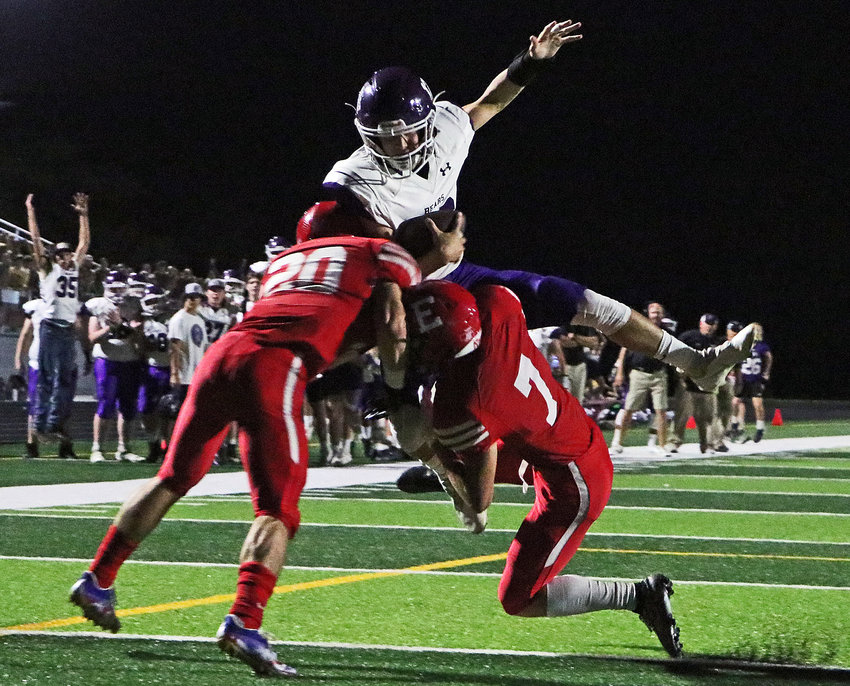 Blair quarterback Bode Soukup leaps into Antlers Mikey Hart, left, Cole Houck and the end zone Thursday at Elkhorn High School. The touchdown gave BHS a lead, but second-ranked EHS came back to win, 23-21.