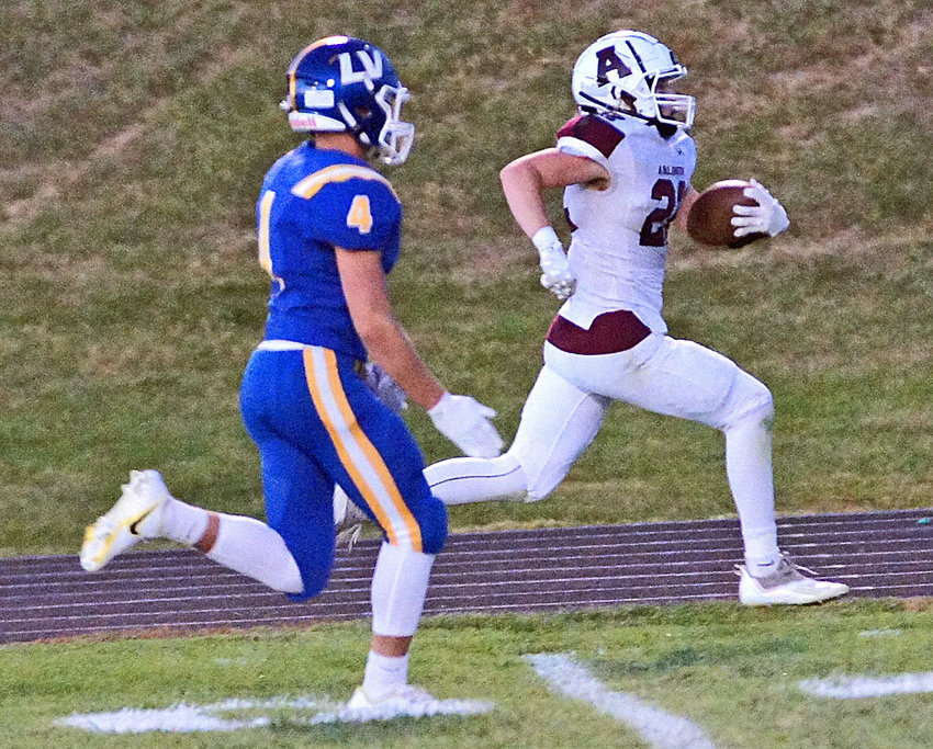Arlington Eagle Nick Smith races down the sideline for a second quarter touchdown as the Raiders' Alex Foust gives chase Friday at Logan View High School.