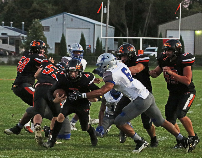 Pioneers quarterback Ty Hallberg, middle left, carries the ball as Boys Town's Colin Propps closes in Friday at Fort Calhoun High School.