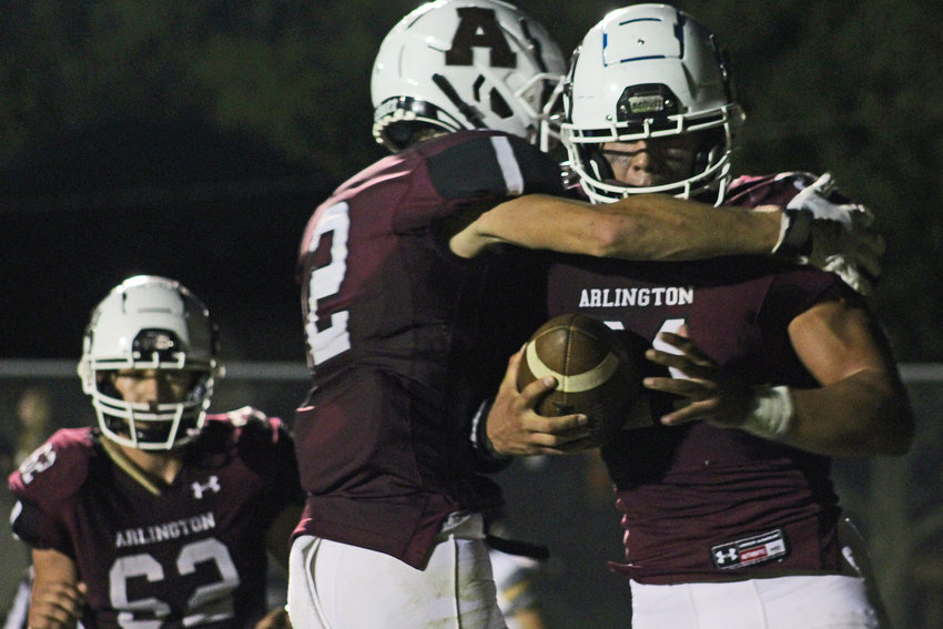 Eagles senior Collin Burdess, right, celebrates a touchdown with Dustin Kirk, middle, and Weston Wollberg on Friday at Arlington High School.