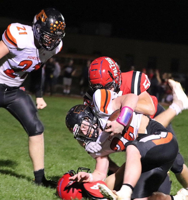 Fort Calhoun's Clint Dierks finishes off a run as the Pioneers' Zane Schwarz (21) moves in to help Friday at Douglas County West High School.
