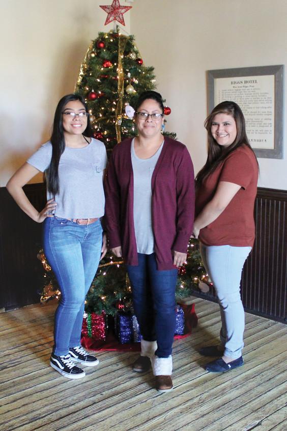 Jazmine Trevino, Melba Montoya, and Magali Rivera stand united beside the Annie Riggs Memorial Museum's 2017 Christmas tree.