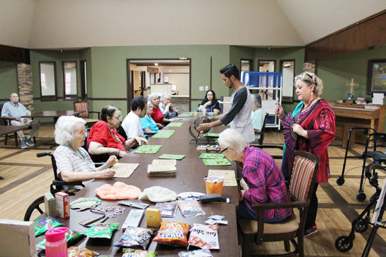 The residents at the Living & Rehab nursing home keep their eyes locked on their bingo cards in hopes of winning one of the many prizes at the head of the table.