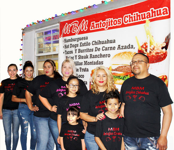 Husband and wife, Gilbert and Griselda Arcides, stand outside of their MBM Antojitos Chihuahua food trailer with their staff of family and close friends.