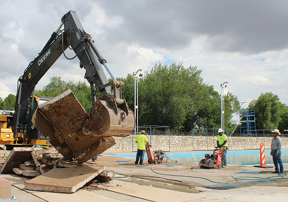 Work began Monday, July 9 on the Comanche Springs Swimming Pool repairs on Monday, July 9. Precinct 2 Commissioner Lupe Dominguez (far right) watches as the first slabs of concrete surface were removed.