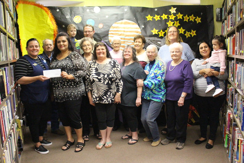 Magda Montferrand, far left, of the Walmart in Fort Stockton, presented a $2,500 check from the store to the Imperial Public Library on Monday, March 25. The funds will be used for books, prizes, decorations and other items needed during the library's extensive summer reading program for children.