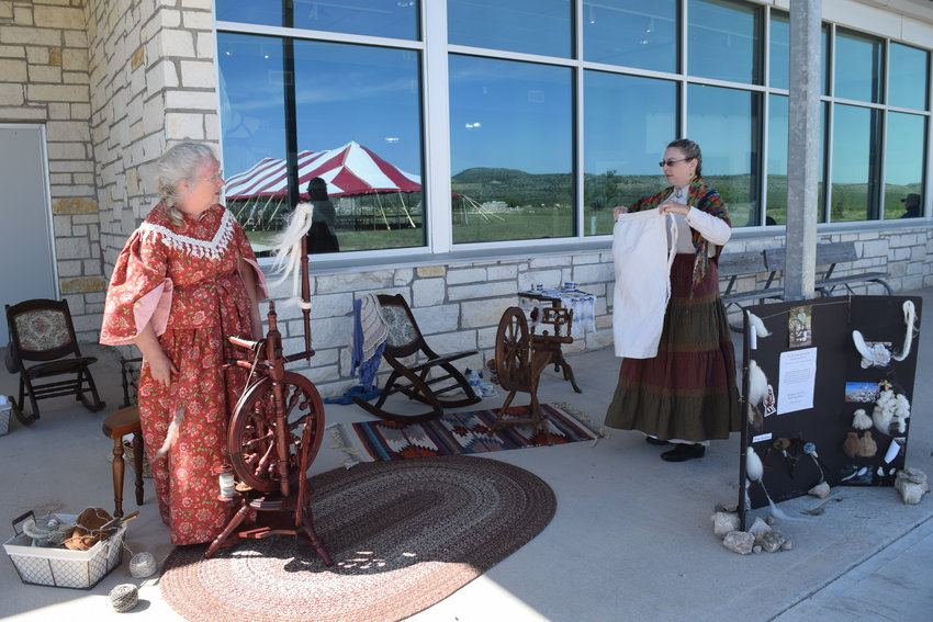 Allson Walkinson of Brackettville and Tanya Petruney of Comstock are shown spinning cotton flax, some with camel hair within. (Kim Dutton/For The Pioneer)