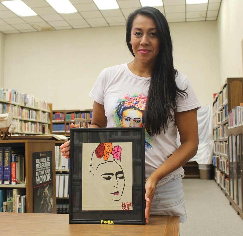 Peadra Onsurez poses with her drawing of Frida Kahlo.