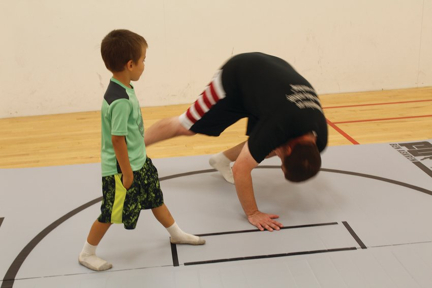 Mike Belcher shows one of his younger students, Maximus Rivera, 5, how to do a tumble.