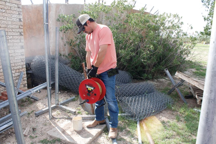 A small exempt well at the City of Fort Stockton Cemetery gets checked by a large tape measurer with a probe at the end telling Field Technician Anthony Bodnar how far until they reach water. For this particular well it was 139 feet.