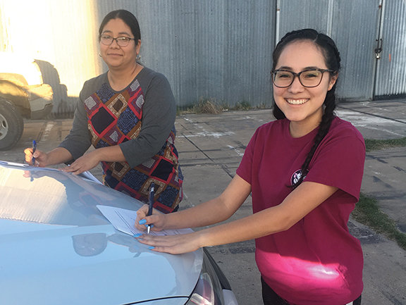 """Dalila Lara, left, and Kaitlynn Pacheco, right, sign the director contracts for the Water Carnival on a car hood while social distancing last week. The duo created the winning script: """"How NOT To Propose In Vegas."""""""
