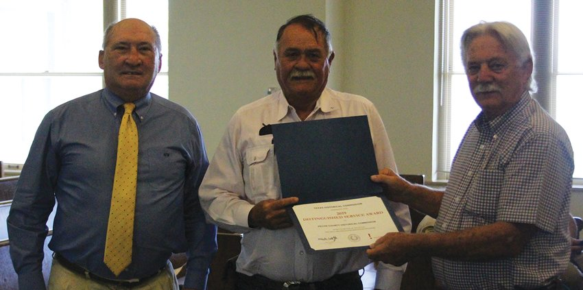 The Pecos County Historical Commission received a 2019 Distinguished Service Award from the Texas Historical Commission prior to the July 13 meeting of the Pecos County Commissioners Court. Commission member Kirby Warnock, left, and president Ernest Woodward, middle, were on hand to receive the award from Judge Joe Shuster.