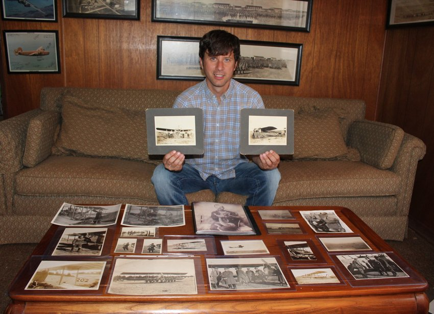 Early aviation historian Jacob Stringer poses with his photos of Ralston in his Center Point home.