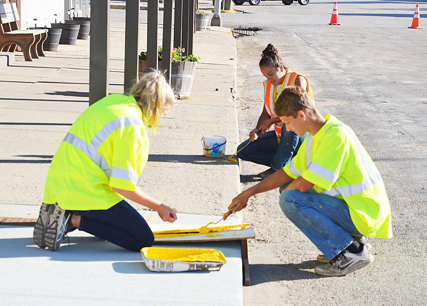 On June 11, De Smet city summer employees Reyna Beck, rear, Cori Birkel, front left, and Kasen Janssen paint parking stripes on the sidewalk along Calumet Avenue. The employees also work at the city swimming pool.