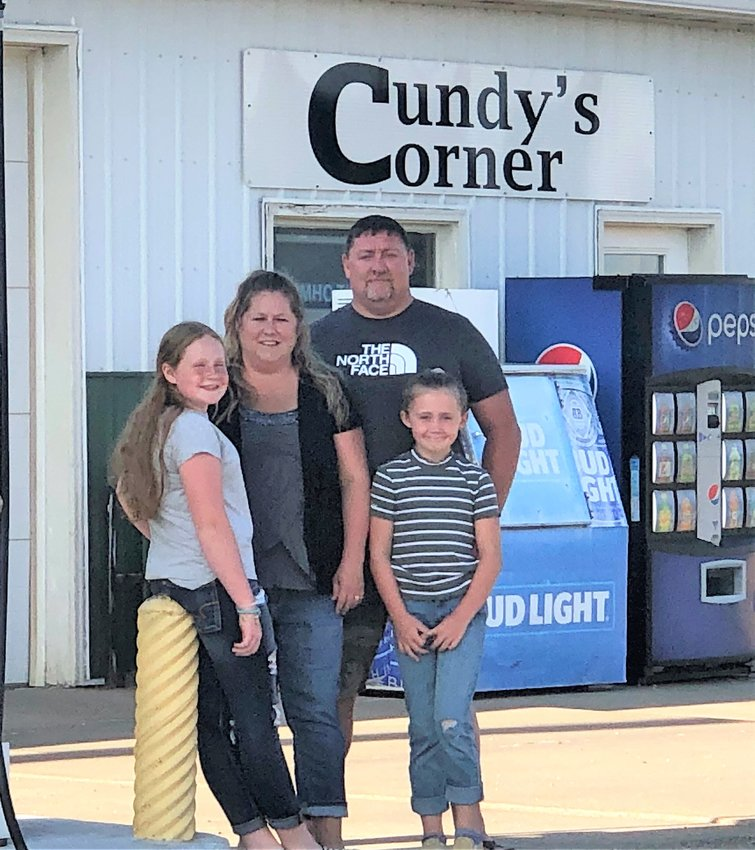 Jill, rear left, and Brian Cundy and their daughters Natalie, front left, and Madelyn stand in front of the family business in Iroquois. The Cundys have put the gas station and convenience store up for sale.