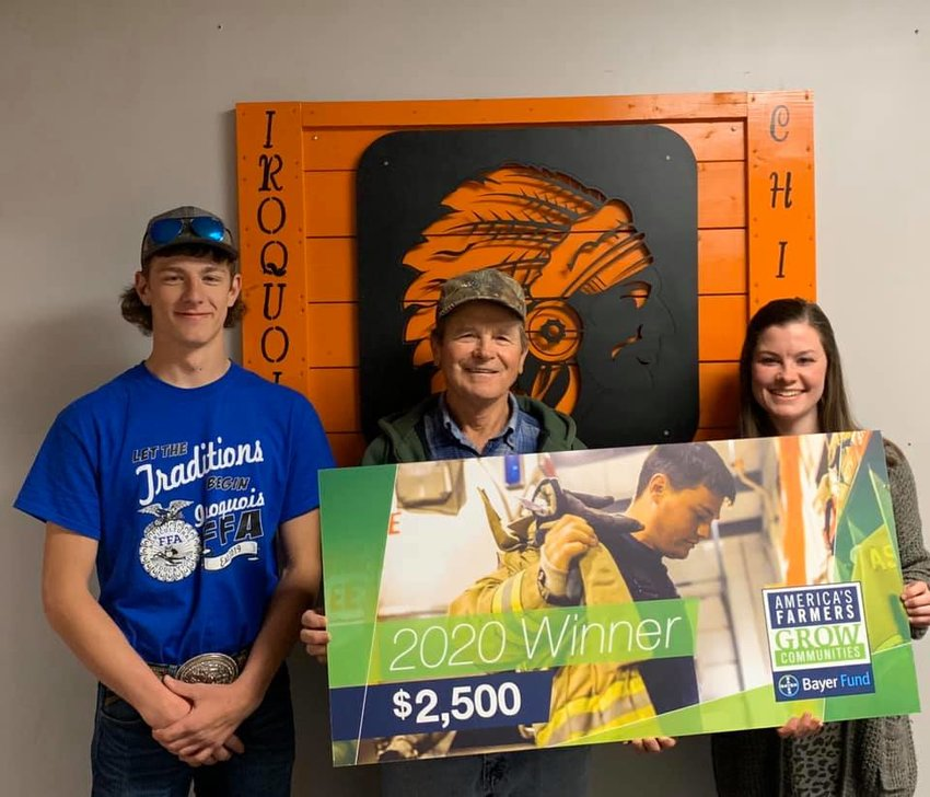 Greg Blue, center, presents a check to benefit the Iroquois School Ag program to student Shawn Diehl, left, and teacher Breanna Mueller.