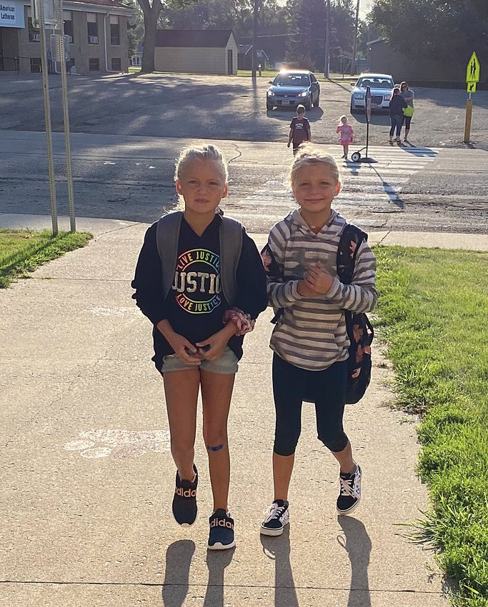 Sisters Kenna, left, and Tegan Currier arrive Aug. 21 for their second day of school at De Smet.