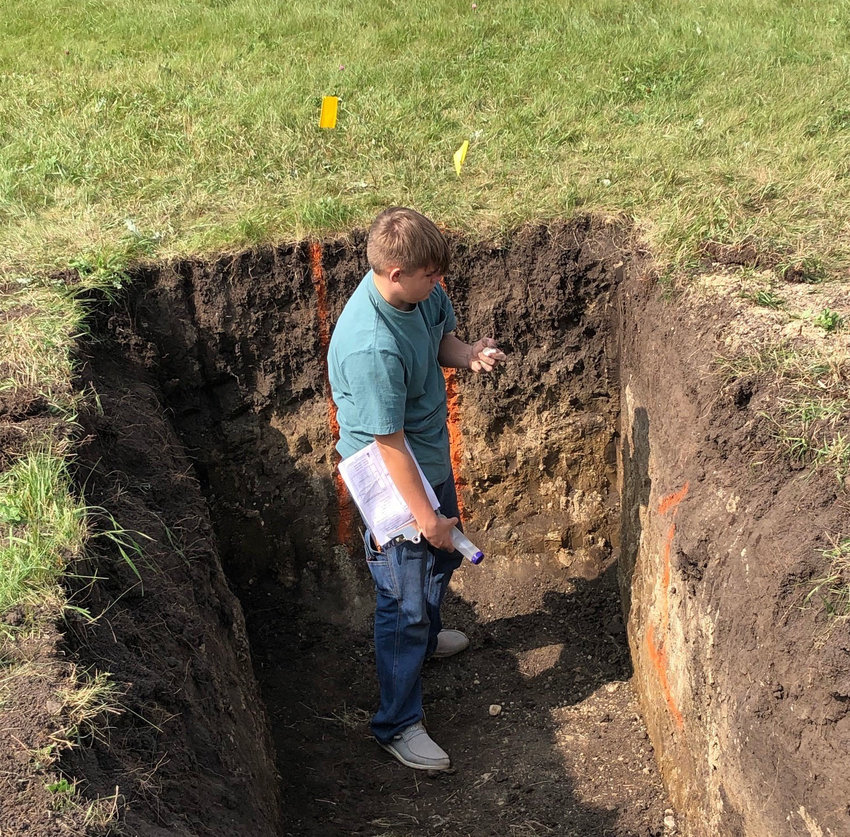 Tucker Holland finds the slope and examines the soil.