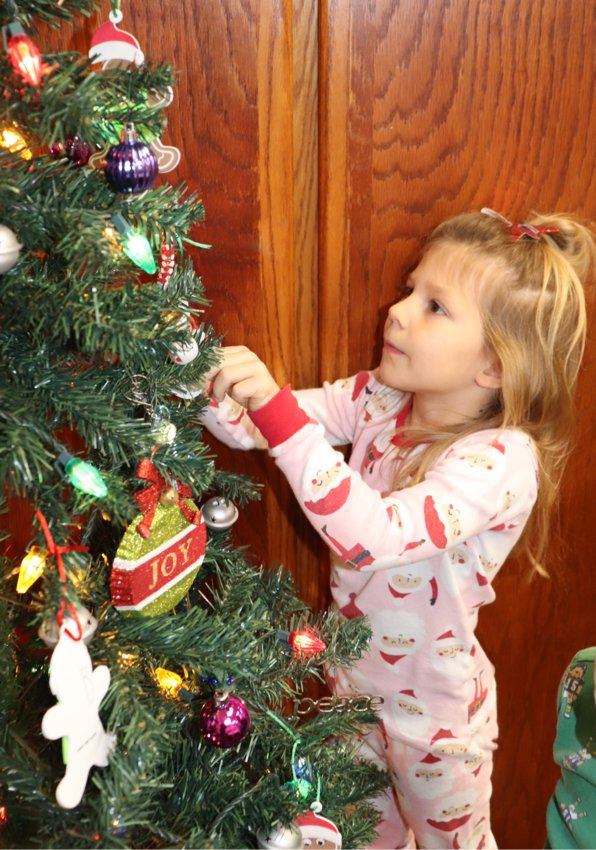 Lake Preston School has started celebrating Christmas, and they are rocking it! Last Friday was North Pole dress up day, and Monday was pajama day.  Hattie Hesby, daughter of Tyler and Emily Hesby, puts her ornament on the Christmas tree in her Santa pajamas.