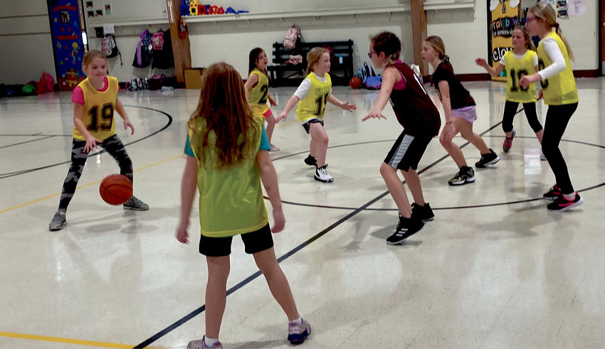 The De Smet fourth-grade girls basketball team works on some of the basics with members of the second-grade team.
