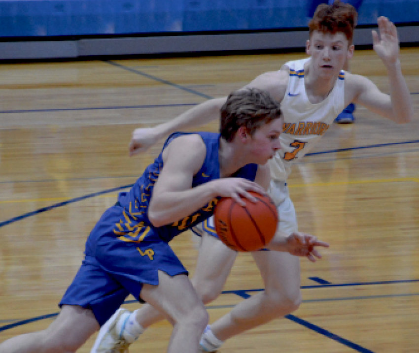 Tate Larsen drives by a Warrior defender.