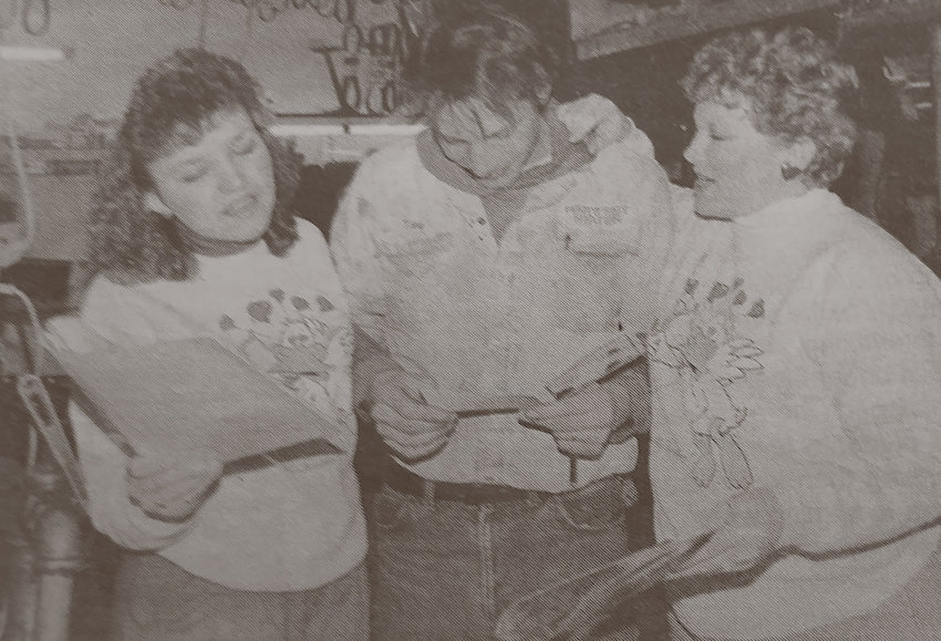 Tony DeKnikker, middle, listens as Singing Valentines Julie Sampson, left, and Janna Odden deliver a sweet song ordered by Tony's wife, Darlene. Sampson and Odden delivered 23 musical messages for Valentine's Day this year. Proceeds are given to the Kingsbury Memorial Manor.