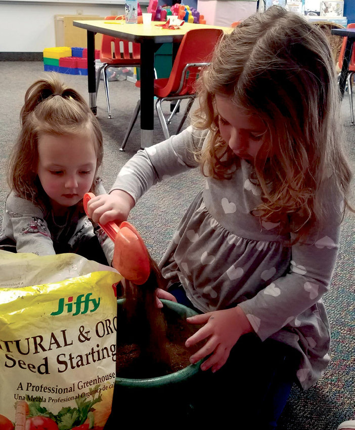 """Savannah Driggers and Jordyn Van Diepen plant a mitten after reading """"The Missing Mitten Mystery."""""""