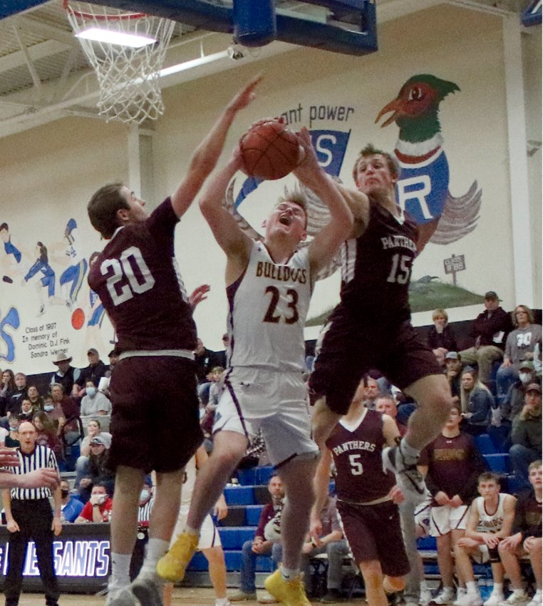 De Smet Bulldog Cody Cavanaugh meets resistance from two Timber Lake Panthers up high. The Bulldogs won the March 9 SoDak 16 match-up in Redfield 64-38. This win has the De Smet boys' basketball team heading to state in Aberdeen, March 18–20.