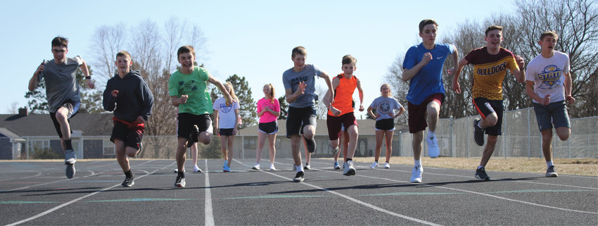 Middle and high school runners Brayden Roth (left), Tanner Tolzin, Slayten Wilkinson, RJ Cleveland, Chase Temme, Clayton Crowe, Noah Roth and Kayden Fast practice their sprints, while the girls' team waits their turn at the starting line. The track and field team will have their first meet in De Smet on April 15.
