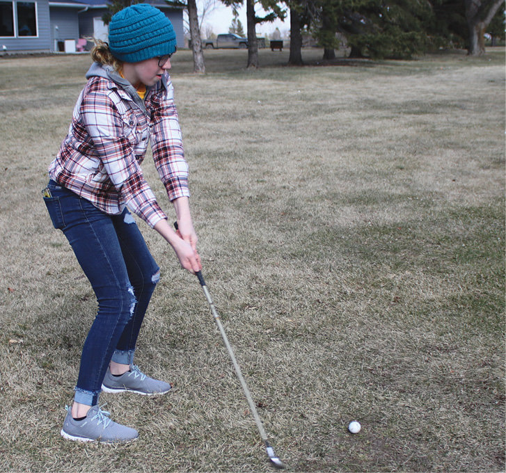 Ivey Schoenfelder is just about to connect in a drive to the green. On the second day of golf practices, temperatures were in the thirties, and the wind was blowing with gusts up to forty miles an hour. Despite the uncooperating weather, the golf team was still out there swinging away.