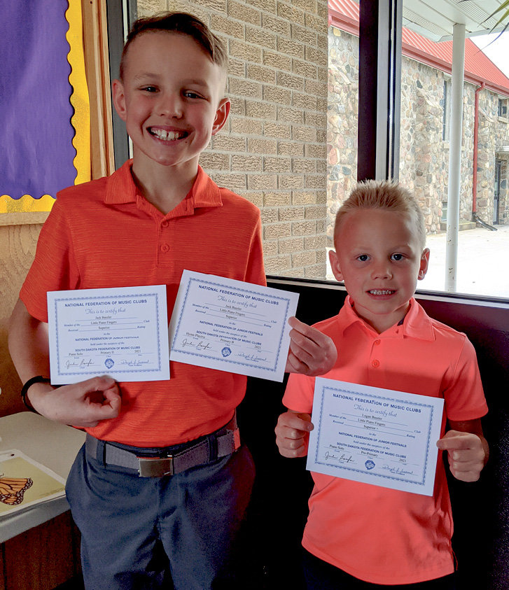 Jack (9) and Logan (6) Baszler holding piano festival superior certificates.