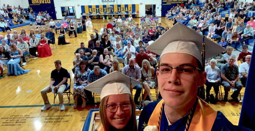 Carter Malone and Mirra Rhodes take an epic selfie with the crowd during their co-valedictorian graduation speech.