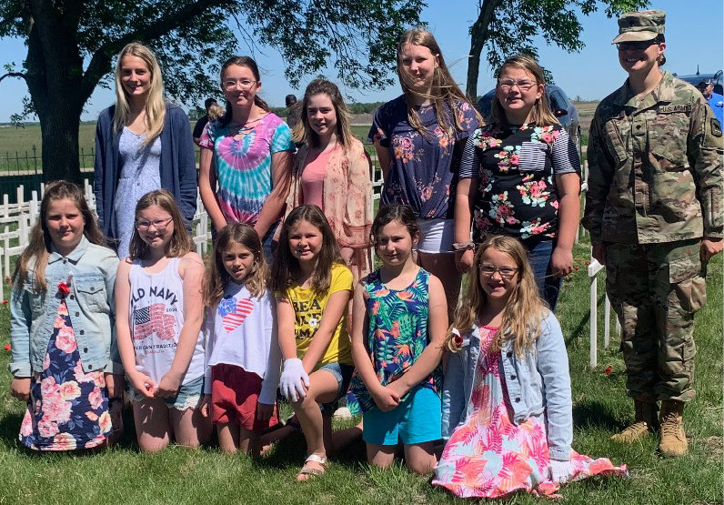 After the Oldham Memorial Day Service, some made their way to the cemetery to put wreaths on the crosses of the men and women who fought. Volunteers included Stella DeKnikker, back left, Iryland Schultz, Autumn Clark, Katie Brown, Jenna Winselman and SPC Kristen Longville. Front left, Gentry Murphy, Allie Brown, Claire Murphy, Hayden Schultz, Erika Krogman and Macey Josephsen.