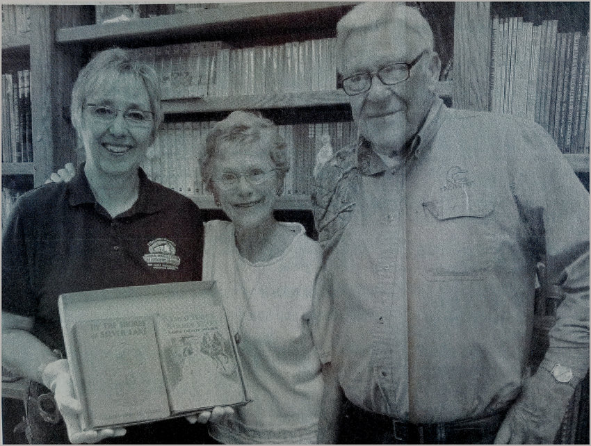 """TEN YEARS AGO: Cheryl Palmlund, left, manager of the Laura Ingalls Wilder Memorial Society, and Phyllis and Bob Bell, with the signed first-edition copies of Laura Ingalls Wilder's books """"By the Shores of Silver Lake"""" and """"These Happy Golden Years"""" that the Bells have donated to the society."""
