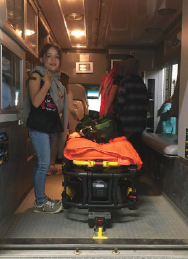 Mikayla Arbeiter investigates the inside of the ambulance.
