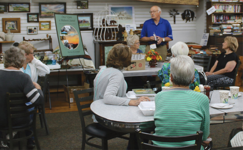 The audience listens intently as Delmer Wolkow talks about his little sister, DeAnn Kruempel, seated to his left in the black top, and the books she has written. Kruempel was in town last Friday for a book signing hosted at Ward's Store and Bakery.