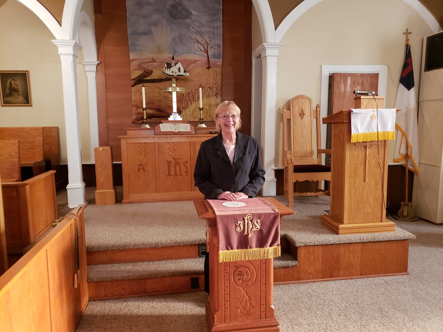 Rev. Marjie Brewton, in her twentieth year serving as the congregation's pastor, stands behind the original church pulpit.  The congregation is also in possession of a star quilt constructed by the mother of James Erwin Hollister.