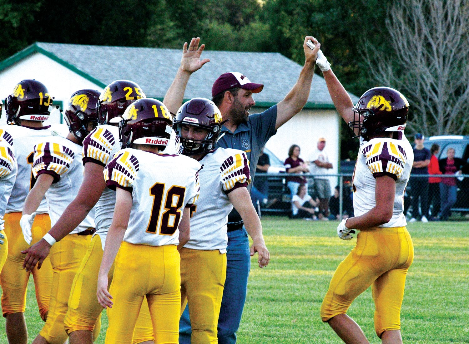 Coach Dan Wilkinson congratulates players coming off the field to a big win over the Cardinals in Dell Rapids.
