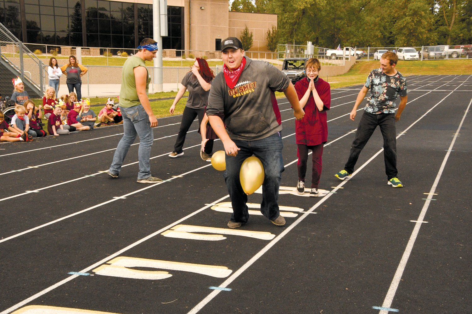De Smet seniors, Kain Gilligan, left, Caitlyn Brag, Trevor Benthin, Carly Wiese and Andy Close participated in  a relay during Friday's pep-fest. The elementary students enjoyed cheering them on.