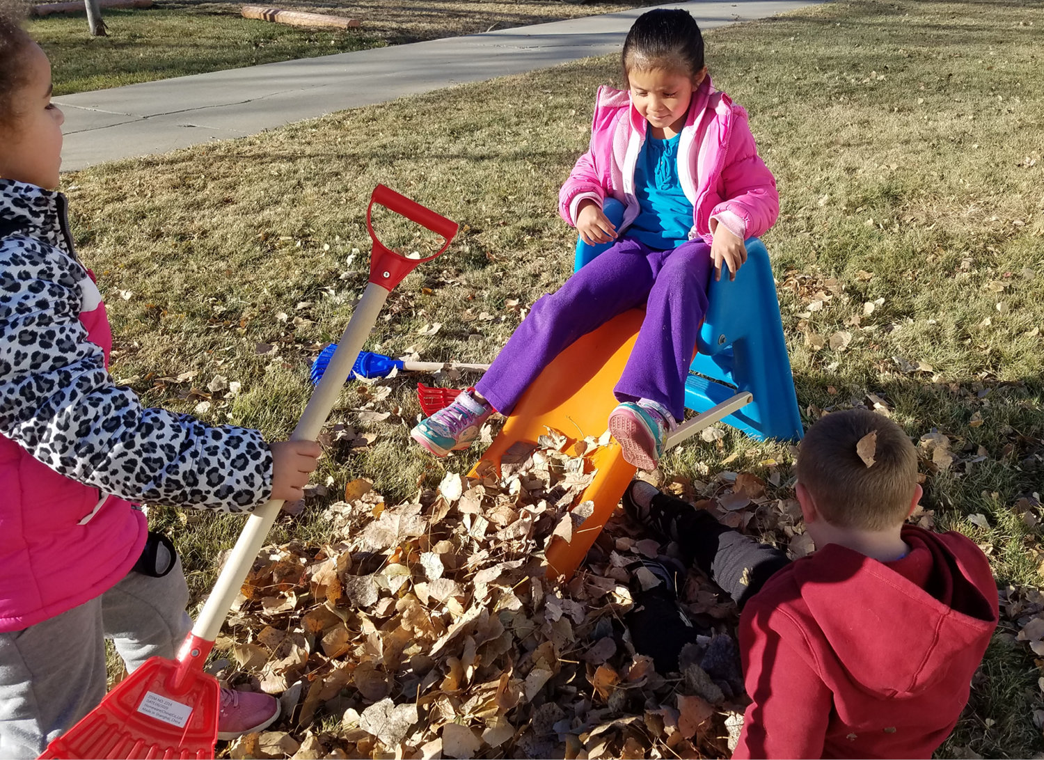 Elienai Hernandez, Sarai Hernandez and Nathan Wipf play in the leaves during a beautiful December day.